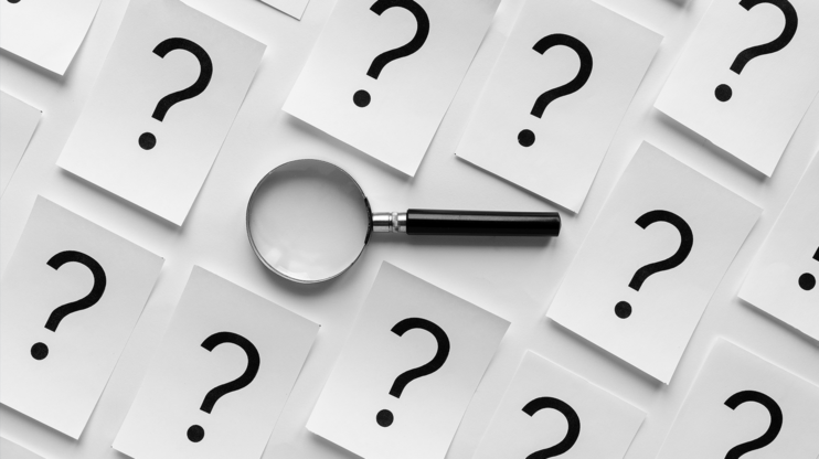white papers with question marks on them, on top of it a magnifying glass